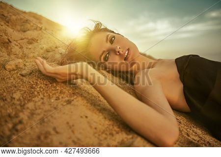 Fashion shot. Gorgeous young woman in black dress lies on the sand in the desert at sunset.