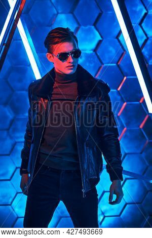Men's style and fashion. Portrait of a courageous handsome man in black sunglasses and black leather jacket posing among neon lamps. Futurism, techno style.