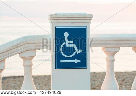 International Disability Day. A Blue Sign With A Handicapped Person On The Public Beach. Concept Of