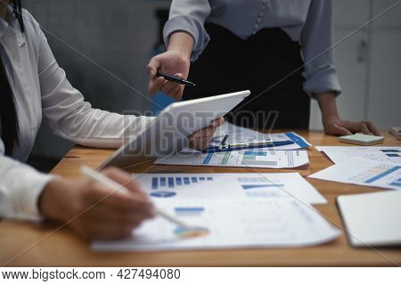 Fund Managers Teams Researching And Analysis Investment Stock Market By Paperwork On Wooden Desk In