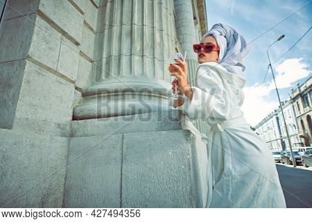 Glamorous lifestyle. Stunning woman in a white terry dressing gown with a white towel on her head alluring on a city street with a glass of champagne and cigarette. Fashion shot.