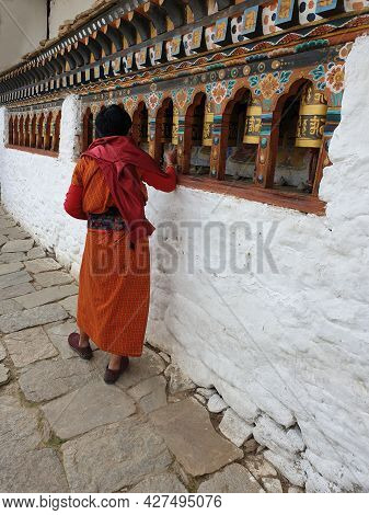 Thimpu, Bhutan - May 02, 2019: A Bhutanese Monk Rolling The Bells Outside A Traditional Temple As A