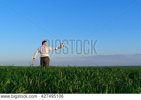 businessman poses with soccer ball in a green grass field - freelance, sport and business concept