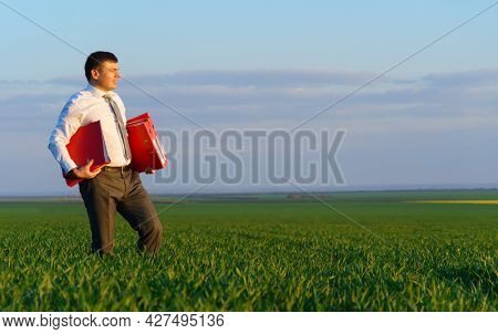 businessman walks through a green grass field and holds an office red folder with documents - business concept
