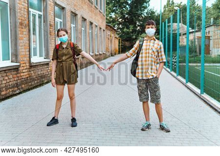 two teenagers boy and girl on the way to the school, they use protective face mask and show social distance to protect against coronavirus infection