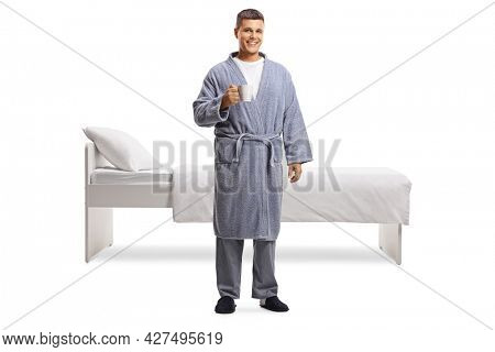 Full length portrait of a man in a bathrobe holding a cup in front of a bed isolated on white background