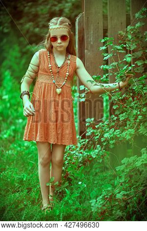 Romantic hippie style. Full length portrait of a cute girl child dressed in hippie style standing by fence in countryside.