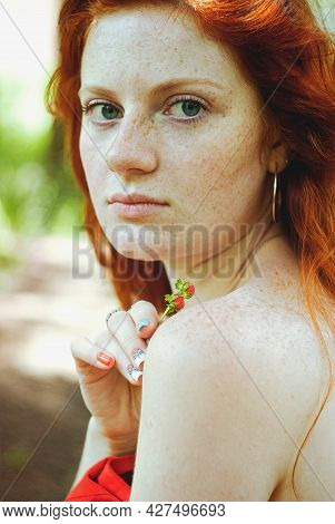 Stylish Girl With Freckles And Red Hair In Red Long Dress Holding Red Poppy Flower At Green Field On
