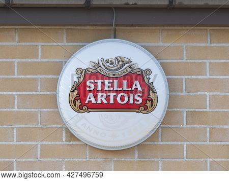 Sint Gillis Waas, Belgium, July 11, 2021, Round Sign Against Brick Wall With The Logo Of The Stella