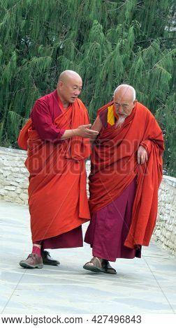 Thimpu, Bhutan - April 30, 2019: Two Senior Buddhist Monks In Bhutan Walking Down A Path.