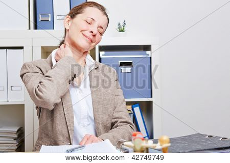 Senior business woman stretching with neck pain in her office