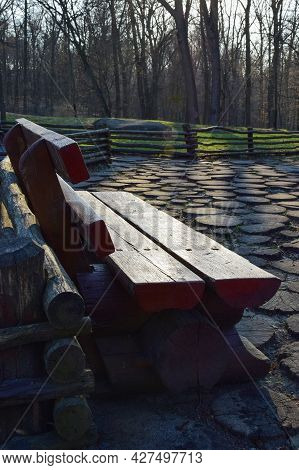 Wooden Carved Park Bench Made Of Thick Logs In A Summer Forest With Wood Covering