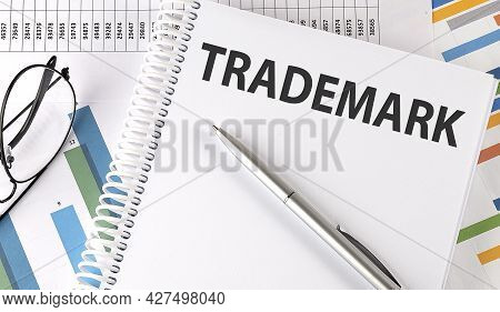 Trademark Text , Pen And Glasses On Chart,business