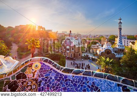 Barcelona city view from Guell Park with colorful mosaic buildings in tourist attraction Park Guell in the morning on sunrise. Barcelona, Spain