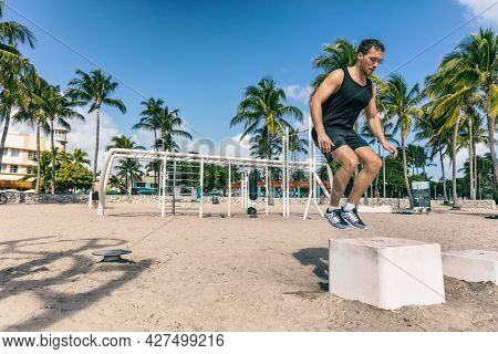 Training squat jumping on box in outdoor beach gym. Man athlete workout at Fitness bench jumping at Miami Beach . Strength training exercise fit male working out outdoors.