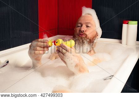 Cute Funny Bearded Man Playing With Rubber Ducks In Bubble Bath Relaxing At Home.