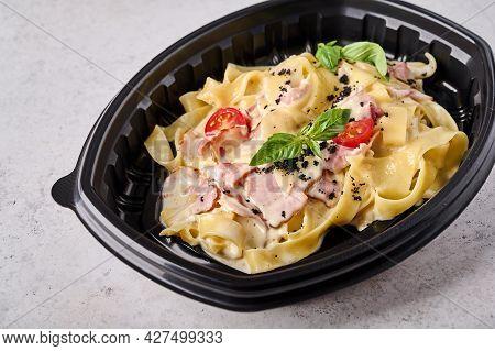 Tagliatelle Carbonara In Black Plastic Container On Light Background Close Up. Designer Food Concept
