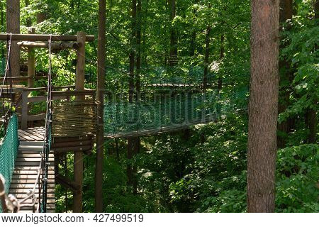 Rope Park With Suspension Bridges Located In The Forest At The Height Among The Lush Foliage Of Tree