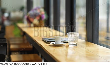Cafe Working Space, With A Glass Of Ice Water, Coffee Cup And Portable Laptop