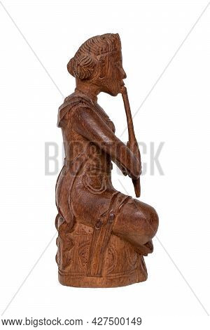 Closeup Of An Antique Carved Wooden Figure Of An Asian Man Sitting And Playing A Musical Instrument.