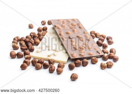 White and dark chocolate bars with hazelnuts isolated on white background.