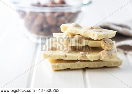 White chocolate bar with hazelnuts on white table.
