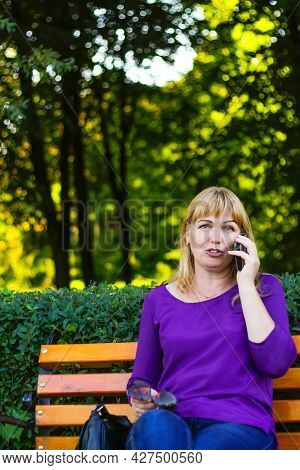 Defocus Caucasian Emotion Blond Woman Talking, Speaking On The Phone Outside, Outdoor. 40s Years Old