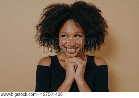 Studio Shot Of Happy Afro Girl Keeps Hands Together Under Chin, Being In High Spirit, Likes Friends