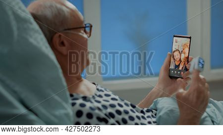 Sick Elder Patient Talking On Videocall With Family In Hospital Ward At Intensive Care Unit. Old Man