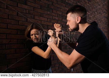 Man Abusing Scared Woman Near Brick Wall. Domestic Violence