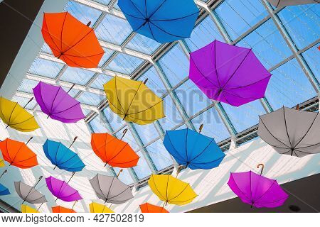 Many Colorful Umbrellas Hanging From The Ceiling Under Glassed Roof