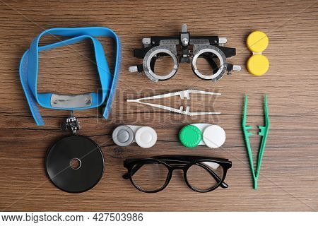 Different Ophthalmologist Tools On Wooden Background, Flat Lay