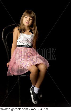 Beautiful Happy Girl Sitting On Chair. Adorable Preteen Girl In Stylish Fashionable Summer Dress And