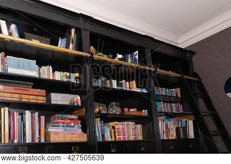 Auckland - New Zealand -  19  July 2021; Dark Timber Bookshelf Crammed With Books And Items For A Ba