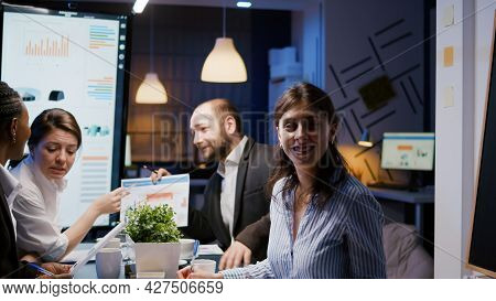 Portrait Of Smiling Businesswoman Looking Into Camera While Sitting At Desk In Company Meeting Offic
