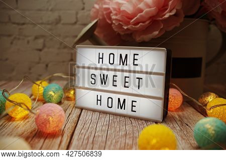 Home Sweet Home Text On Lightbox On Wooden Background
