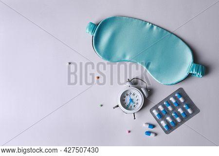 Sleeping Mask, Alarm Clock And Pills On White Background, Flat Lay. Insomnia Treatment