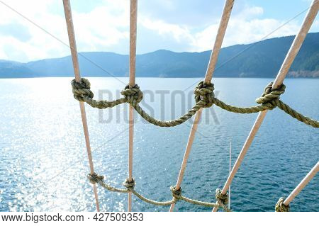 Close Up Detail Of A Shroud On A Sailing Vessel Rigging On Sea And Mountain Range Background In Sunn