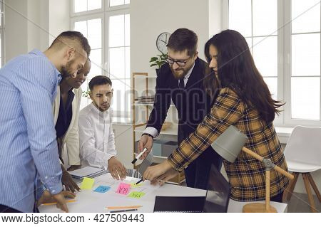 Business Team Writes Notes On Colored Sticky Stickers While Discussing A Startup Project.