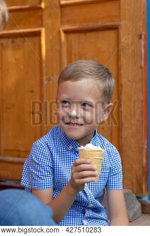 Contented Cheerful Child Boy In A Blue Shirt Eats Ice Cream On The Porch Of A House In A Village On