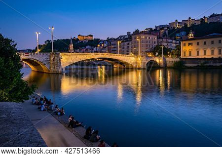Lyon, France - June 11, 2021 : Night view in Lyon city, people relaxing by the river