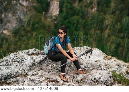 A Woman With A Backpack And Trekking Poles In The Mountains. Woman Hiker With Trekking Poles And Bac