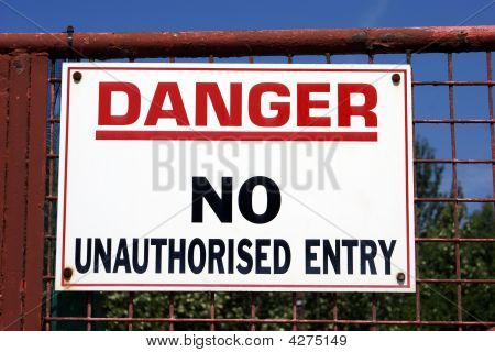 Sign on a metal gate. Danger. No unauthorised entry. poster