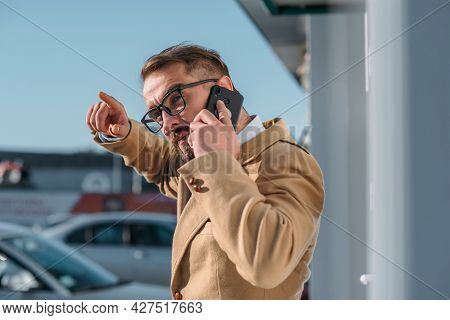 A Man Speaks On The Phone - Close-up On A White City.