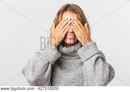 Close-up Of Happy Beautiful Woman In Grey Sweater, Standing Blindsided With Hands On Face, Waiting F