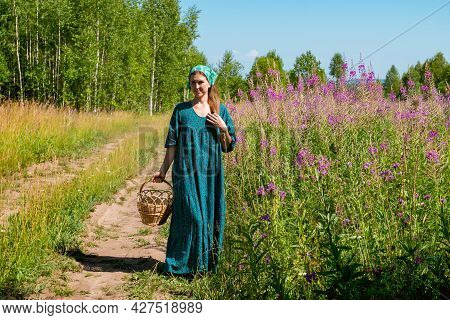 Young Woman In Folk Peasant Clothes With A Wicker Basket Walks Along A Field Road In Summer