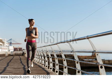 Image Of Attractive Athletic Woman In Sportswear Jogging In The Morning, Looking At Sea And Smiling.