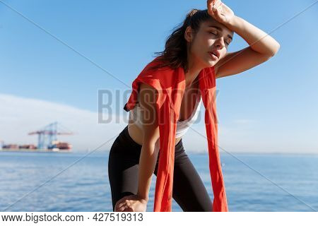 Outdoor Shot Of Tired Young Sportswoman Having A Break Near The Sea, Wiping Sweat And Panting After