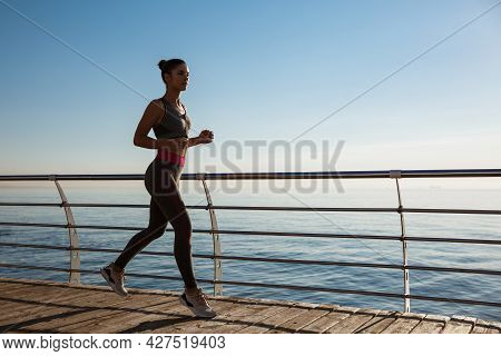 Side View Of Fitness Woman Running Along Seaside Promenade, Workout On Fresh Air Near The Sea