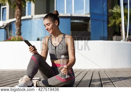 Outdoor Shot Of Happy Attractive Sportswoman Sitting On Floor After Workout, Drinking Water And Look